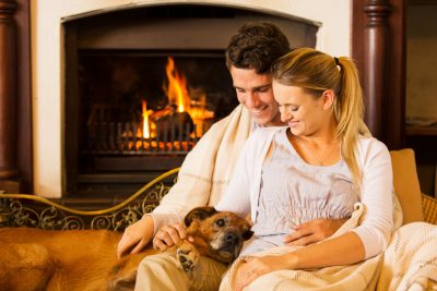Junges Paar sitzt mit Hund vor dem Ofen